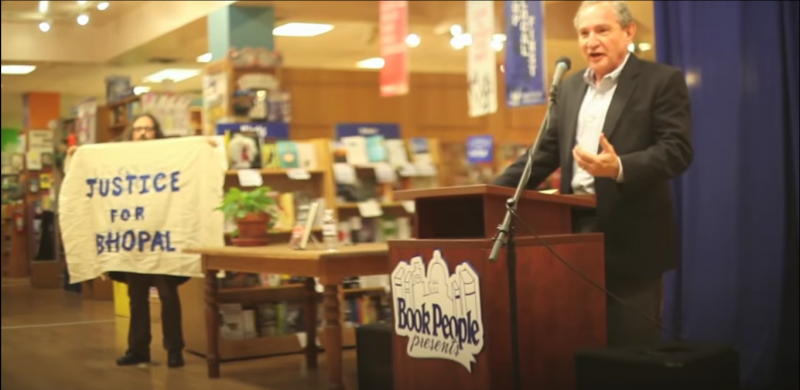 Kit O'Connell confronts George Friedman, CEO of Strategic Forecasting (Stratfor), at a book signing while holding a banner reading Justice For Bhopal. Multiple activists disrupted this event at Book People in Austin, Texas. Emails obtained by WikiLeaks from Anonymous revealed that Dow Chemical paid Stratfor to spy on nonviolent activists seeking justice for the Bhopal, India chemical disaster. (Screenshot)