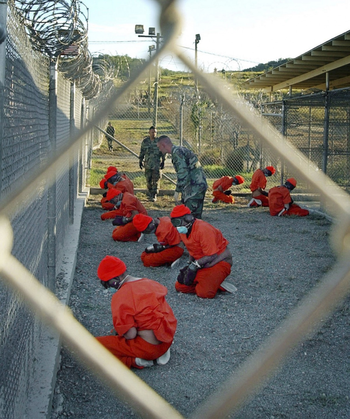 In this Jan. 11, 2002 file photo, released by the U.S. Department of Defense, detainees wearing orange jump suits sit in a holding area as military police patrol during in-processing at the temporary detention facility Camp X-Ray on Guantanamo Bay U.S. Naval Base in Cuba. (AP Photo/U.S. Navy, Shane T.McCoy, File)