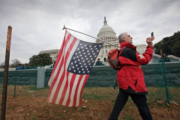 Rit Picone of Newpaltz, N.Y., carries an American flag upside down as a symbol of protest as demonstrators aligned with the Occupy Wall Street movement gathered on Capitol Hill in Washington, Tuesday, Jan. 17, 2012. (AP Photo/J. Scott Applewhite)