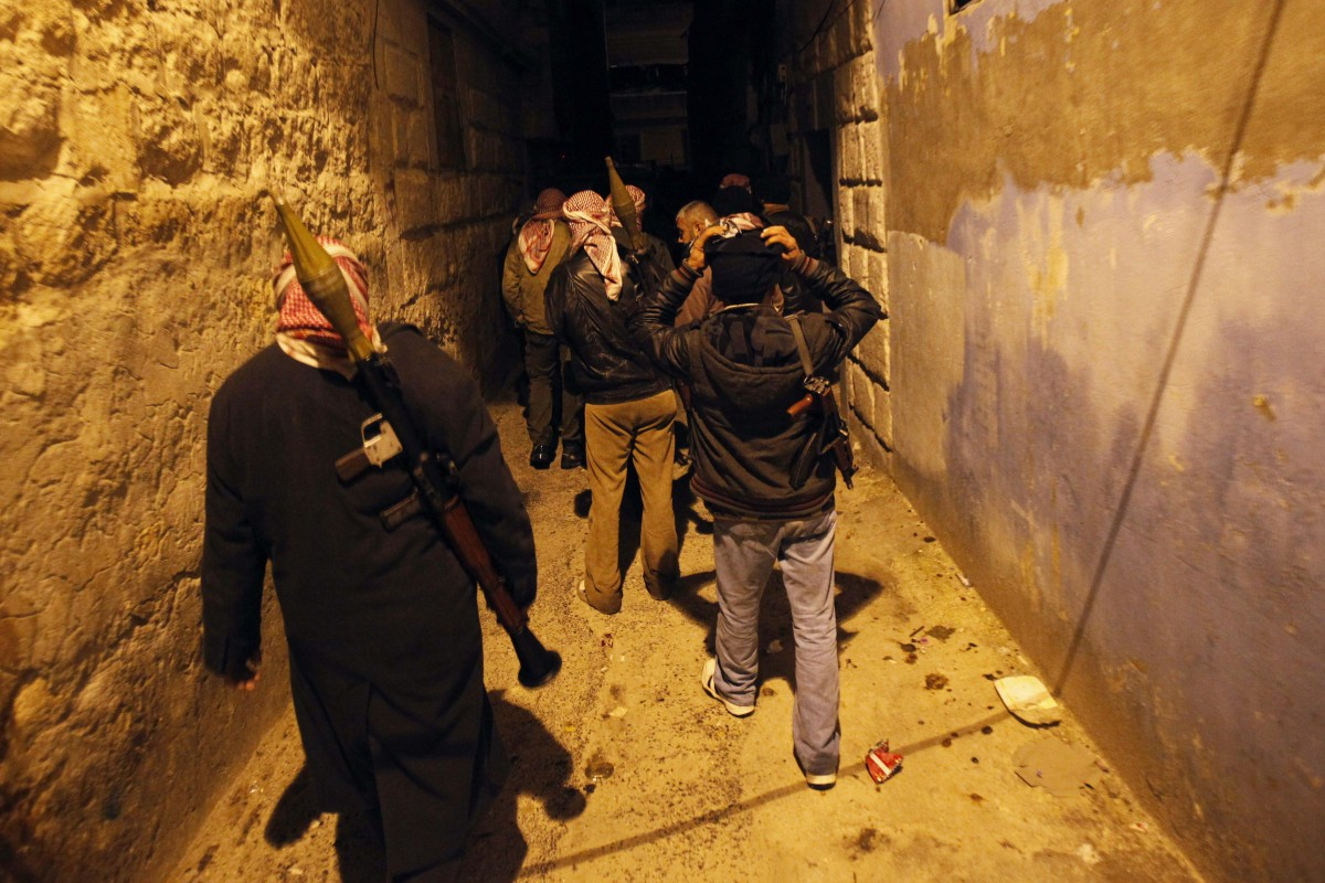 Syrian rebels walk in an alley in Idlib, Syria, Wednesday, Feb. 8, 2012. (AP Photo)