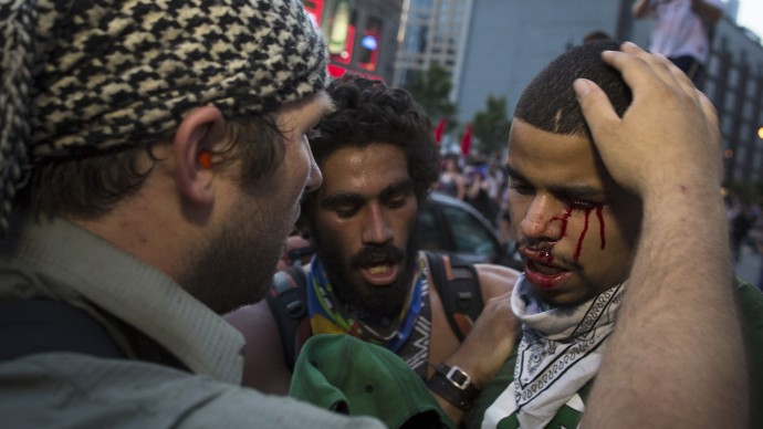 A bleeding anti-NATO protestor is comforted after a scuffle with police during a march in Chicago. (AP Photo/John Minchillo)