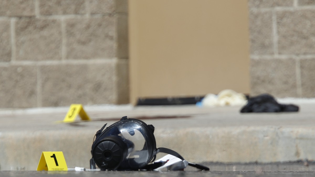 Yellow markers sit next to evidence, including a gas mask, as police investigate the scene outside the Century 16 movie theater east of the Aurora Mall in Aurora, Colo. on Friday, July 20, 2012. (AP Photo/David Zalubowski)