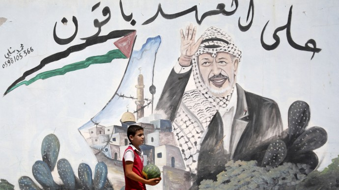 "A Palestinian youth walks next to a mural depicting late Palestinian leader Yasser Arafat, in the northern West Bank village of Kabatyeh, Wednesday, July 4, 2012. Arabic text quotes a famous idiom meaning ""We are holding to our promise."" (AP Photo/Mohammed Ballas)"