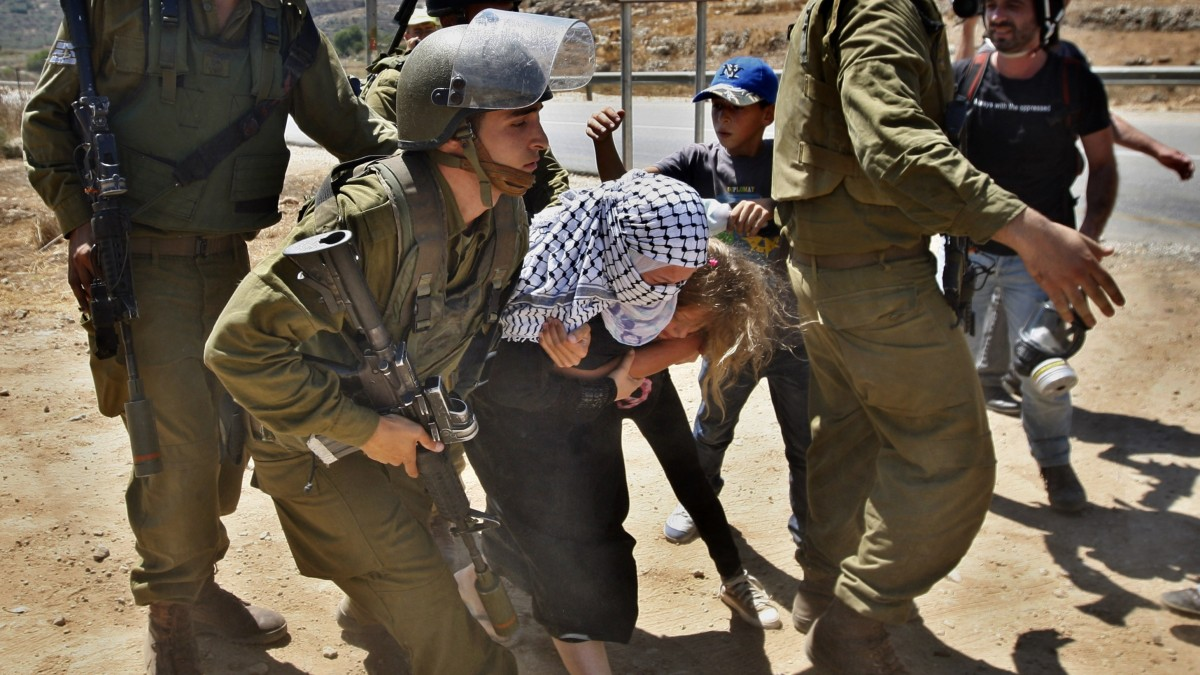 Two Palestinian children try to help Palestinian Nariman Tamimi avoid arrest by Israeli soldiers during a protest against the expansion of the nearby Jewish settlement of Halamish in the West Bank village of Nabi Saleh near Ramallah, Friday, Aug 24, 2012. (AP Photo/Majdi Mohammed)
