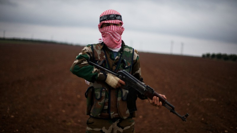 A Free Syrian Army fighter takes position close to a military base, near Azaz, Syria, Monday, Dec. 10, 2012. (AP Photo/Manu Brabo)