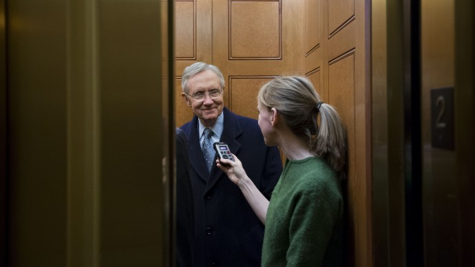 Senate Majority Leader Harry Reid, left, from Nevada, talks with a journalist as the elevator doors close as he departs the Capitol after a vote about the fiscal cliff, on Capitol Hill Tuesday, Jan. 1, 2013 in Washington. (AP Photo/Alex Brandon)