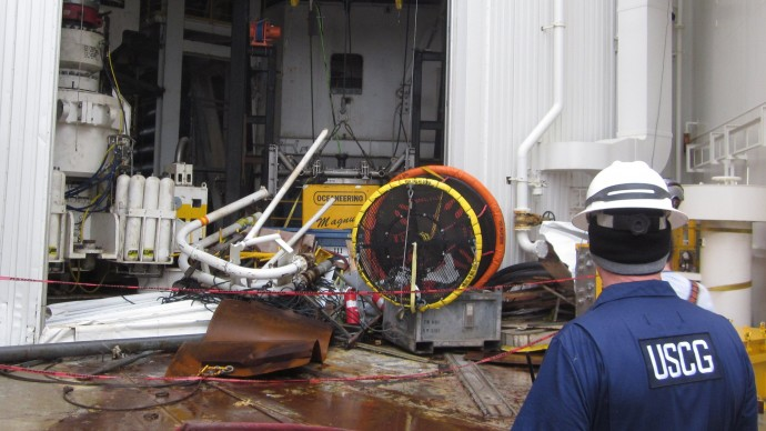 This Jan. 10, 2013, photo provided by the U.S. Coast Guard shows an inspector surveying damaged parts and equipment aboard the Shell Arctic drilling rig Kulluk in Kiluida Bay, near Kodiak, Alaska. (AP Photo/U.S. Fish and Wildlife Service)