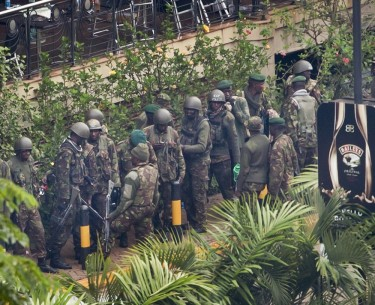 Soldiers from the Kenyan Defence Forces gather at the entrance to the Westgate Mall in Nairobi, Kenya Thursday, Sept. 26, 2013. Working near bodies crushed by rubble in a bullet-scarred, scorched mall, FBI agents began fingerprint, DNA and ballistic analysis Wednesday to help determine the identities and nationalities of victims and al-Shabab gunmen who attacked the shopping center, killing more than 60 people. (AP Photo/Ben Curtis)