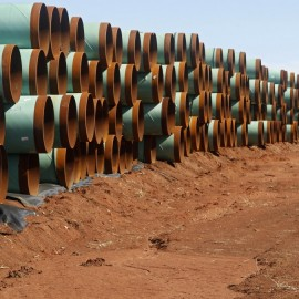 In this Wednesday, Feb. 1, 2012 file photo, miles of pipe ready to become part of the Keystone Pipeline are stacked in a field near Ripley, Okla. (AP Photo/Sue Ogrocki)