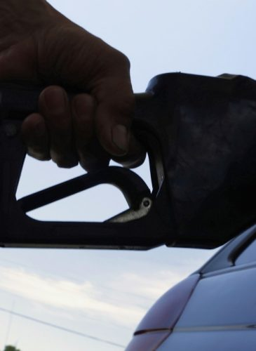 a motorist puts fuel in his car's gas tank at a service station