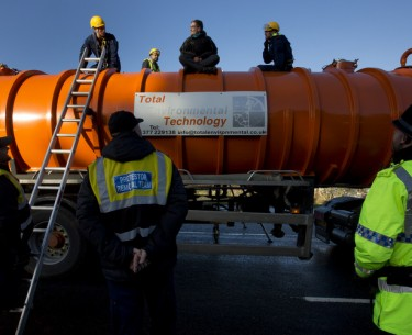 Police prepare to remove a protestor from the top of a vehicle waiting to enter an exploratory drill site for the controversial gas extraction process known as fracking at Barton Moss in Manchester, England, Monday, Jan. 13, 2014. (AP Photo/Jon Super)