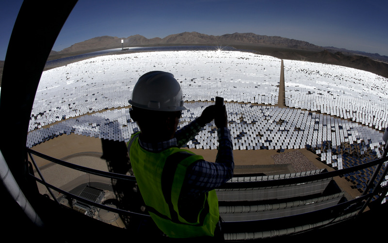 Jeff Holland takes a picture of some of the 300,000 computer-controlled mirrors that reflect sunlight to boilers that sit on 459-foot towers Tuesday, Feb. 11, 2014 in Primm, Nev. The Ivanpah Solar Electric Generating System, sprawling across roughly 5 square miles of federal land near the California-Nevada border, will be opened formally Thursday after years of regulatory and legal tangles. (AP Photo/Chris Carlson)