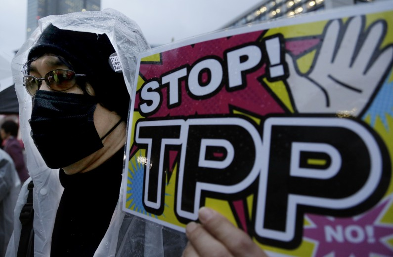 A protester holds a slogan during a rally against the Trans-Pacific Partnership (TPP) in Tokyo, Tuesday, April 22, 2014. (AP Photo/Shizuo Kambayashi)