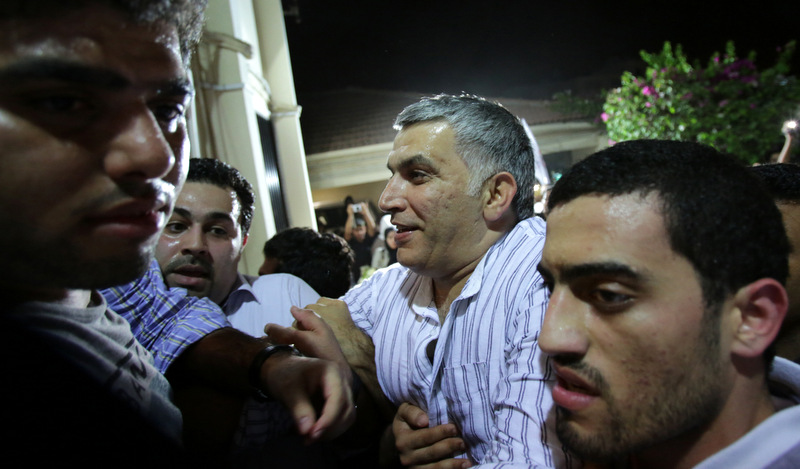 Nabeel Rajab, head of the Bahrain Center for Human Rights, is helped to his front door as well-wishers push in to greet him at his home in Bani Jamra, Bahrain, on Saturday, May 24, 2014, after spending nearly two years behind bars. Rajab was charged sentenced Thursday with an additional six months behind bars for insulting the government on Twitter.