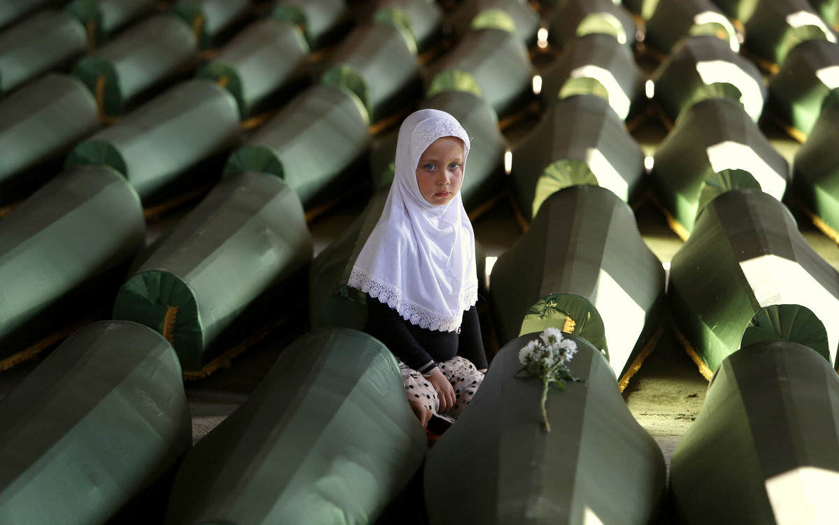 Ema Hasanovic, a young Bosnian Muslim girl, pays her respects near to the coffin of her uncle, in the Srebrenica massacre Memorial center in Potocari, 200 km northeast of Sarajevo, Bosnia, Wednesday, July 9, 2014. (AP/Amel Emric)
