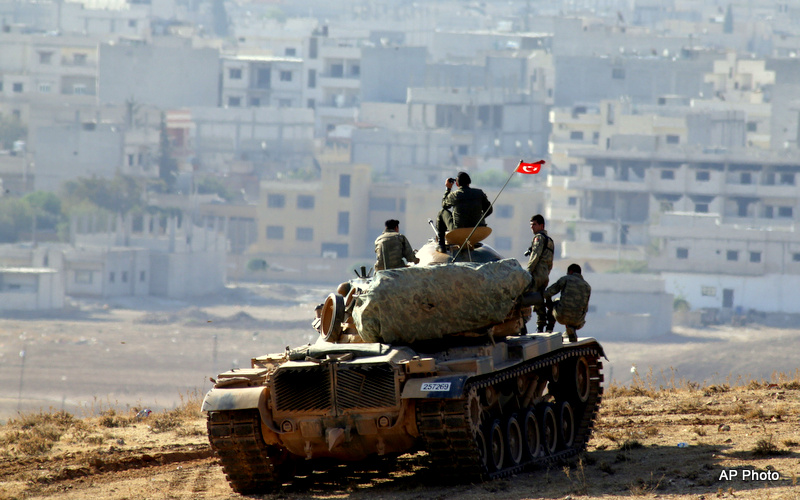 Turkish soldiers on a tank hold their position on a hilltop on the outskirts of Suruc, at the Turkey-Syria border, overlooking Kobani.