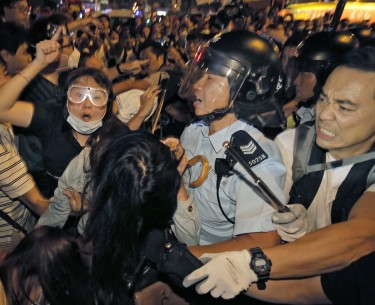 A huge crowd of protesters, some wearing goggles, struggles with riot police.