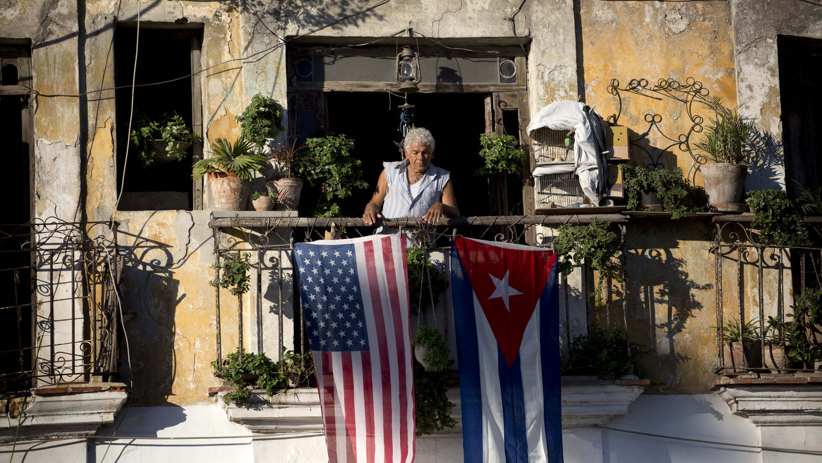 Javier Yanez stands on his balcony where he hung a U.S. and Cuban flag in Old Havana Cuba, Friday, Dec. 19, 2014