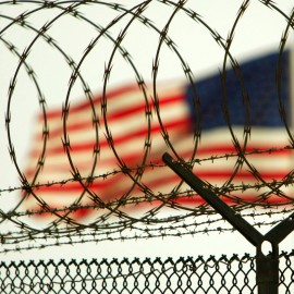 In this photo reviewed by US military officials, an American flag waves within the razor wire-lined compound of Camp Delta prison, at the Guantanamo Bay U.S. Naval Base, Cuba on Tuesday, June 27, 2006. The Supreme Court this week is expected to rule on the legality of President Bush's decision to create U.S. military tribunals for the detainees at Guantanamo, the first such tribunals since World War II.