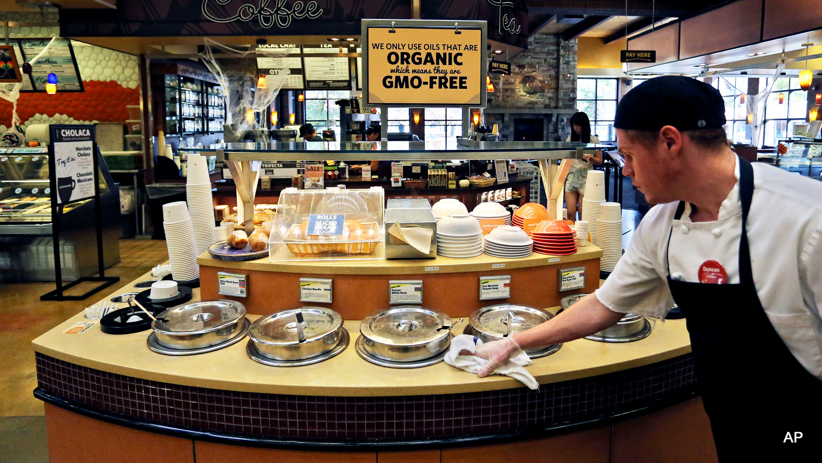 A grocery store employee wipes down a soup bar with a display informing customers of organic, GMO-free oils
