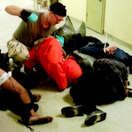 Cpl. Charles A. Graner Jr. punching one of several handcuffed detainees lying on the floor in late 2003 at the Abu Ghraib prison in Baghdad, Iraq. Google has been targeting independent media outlets that publish the Abu Ghraib photos, threatening to cut off vital ad revenue that keep many smaller newsrooms afloat.