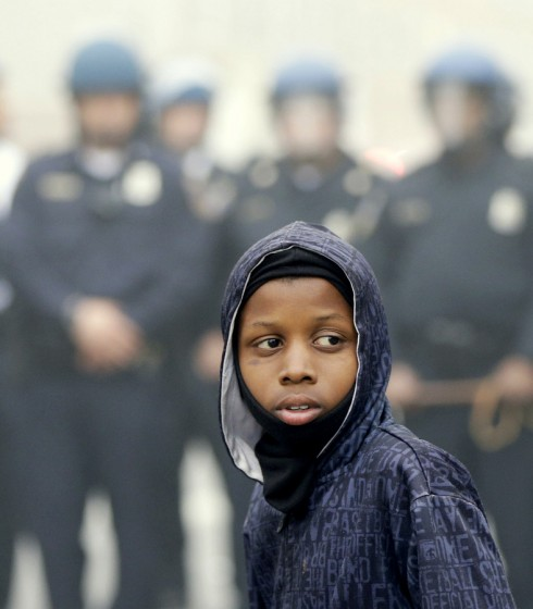 A protestor stands in front of riot Police Monday, April 27, 2015, following the funeral of Freddie Gray in Baltimore.