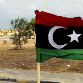 A revolutionary forces commander, Wajdi Badri, right, stands next to a pre-Gadhafi flag as he celebrates the new take over of the western main square in Sirte, Libya, Thursday, Sept. 22, 2011. The general commanding NATO's mission in Libya said at the time that isolated groups of forces loyal to ousted strongman Moammar Gadhafi continud to be a threat to local people would be unable to coordinate their actions.