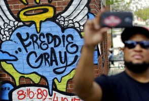 J.R. White, right, takes a selfie in front of a mural that was painted at the site of Freddie Gray's arrest, Saturday, May 2, 2015, in Baltimore, as protesters prepare to march to City Hall.  Six police officers were charged Friday with felonies ranging from assault to murder in Gray's death. In announcing the charges, State's Attorney Marilyn Mosby said police had no reason to stop or chase Gray in the first place when they confronted him on April 12. He died of injuries on April 19. (AP Photo/Patrick Semansky)