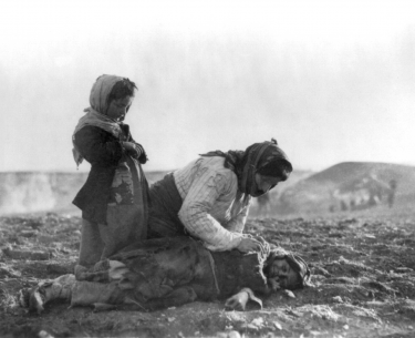 """An Armenian woman kneeling beside a dead child in field """"within sight of help and safety at Aleppo"""", an Ottoman city."""