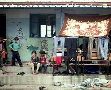 """Palestinian children sit next to hanged clothes, on the First day of Eid al-Fitr in a United Nations school where dozens of families have sought refuge after fleeing their homes in fear of Israeli airstrikes, in the Jabaliya refugee camp, northern Gaza Strip. A U.N. inquiry has found that at least 44 Palestinians were killed and at least 227 injured by """"Israeli actions"""" while sheltering at U.N. locations during last year's Gaza war. Secretary Ban Ki-moon said Monday, April 27, 2015, he deplores the deaths and calls U.N. locations """"inviolable."""""""