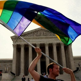 John Becker, 30, of Silver Spring, Md., waves a rainbow flag in support of gay marriage outside of the Supreme Cour