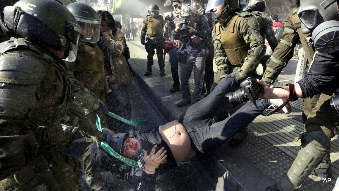 A protester is detained by riot police at the end of a march in Santiago, Chile