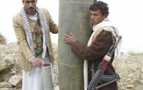 Houthi rebels pose with a US-made cluster bomb shell in northern Yemen.