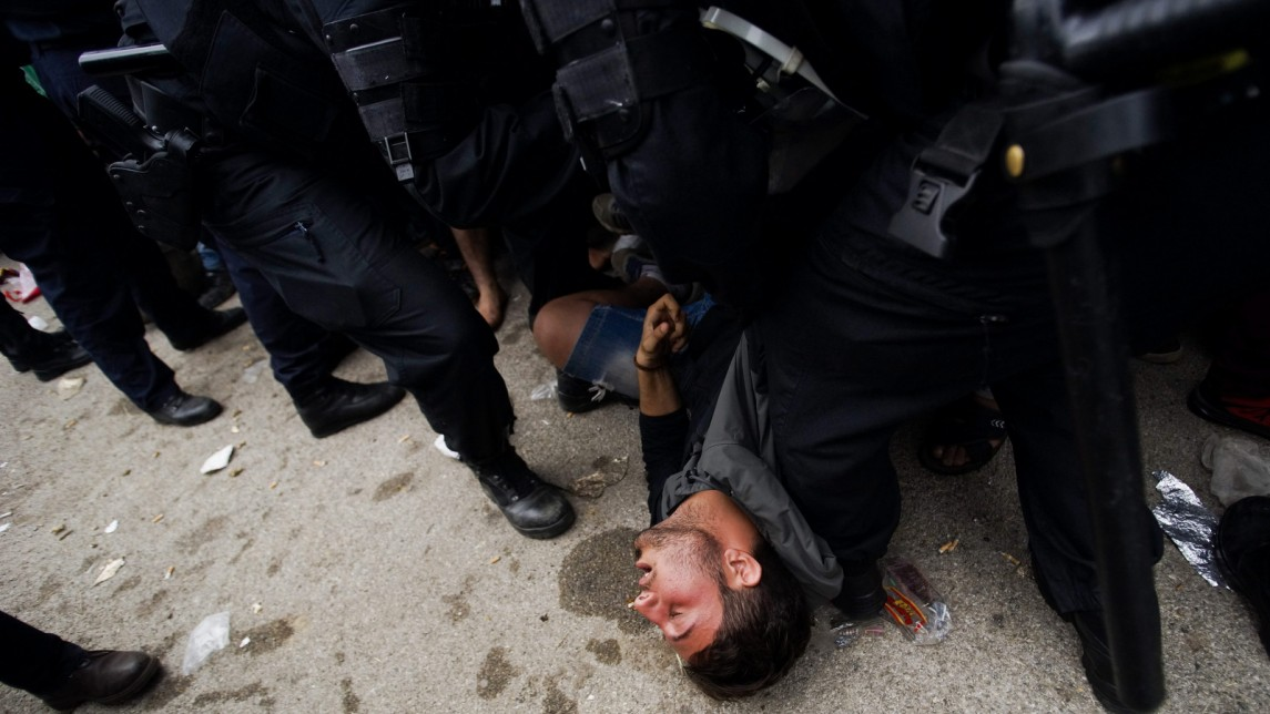A migrant who collapsed from exhaustion lies on the ground next to Croatian police officers in front of a reception center close to Croatia's border with Serbia, in Opatovac, Croatia, Tuesday, Sept. 22, 2015. (Zoltan Balogh/MTI via AP)w