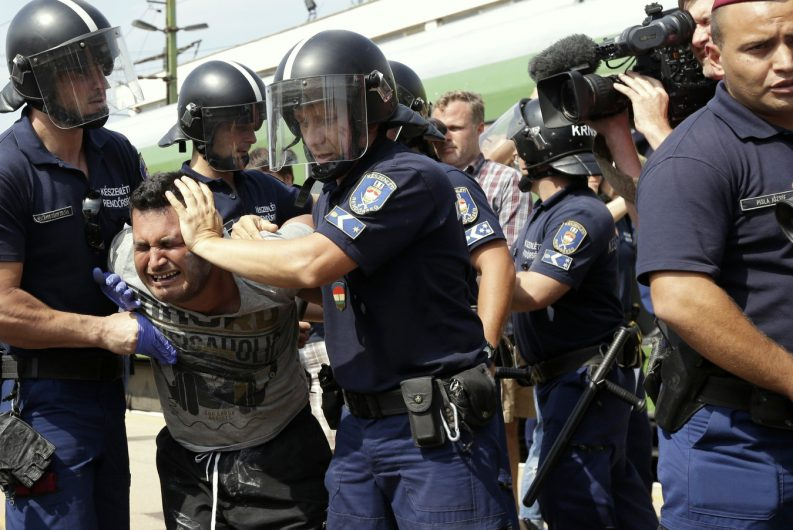 A migrant is detained after the train they were traveling in from Budapest arrived in Bicske, Hungary, Thursday, Sept. 3, 2015. Over 150,000 migrants have reached Hungary this year, most coming through the southern border with Serbia. Many apply for asylum but quickly try to leave for richer EU countries. (AP Photo/Petr David Josek)