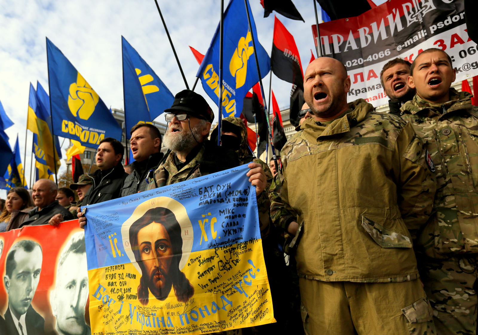 Activists of the of nationalist Svoboda (Freedom) party and members of the Right Sector shout slogans during a rally in Kiev, Ukraine, Wednesday Oct. 14, 2015. Ukraine is marking Defender of the Fatherland Day. (AP Photo/Sergei Chuzavkov)