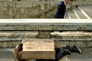 A pedestrian exits a subway station as a homeless man sleeps covered in cardboard packaging, outside the main railway station in Bucharest, Romania, Wednesday, Oct. 7, 2015. The sewers around the railway station are a popular shelter for the town's many homeless, especially in the bitter Balkan winter weather. (AP Photo/Vadim Ghirda)