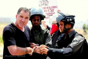 Israeli activist Mike Peled in handcuffs during a protest in Palestine.