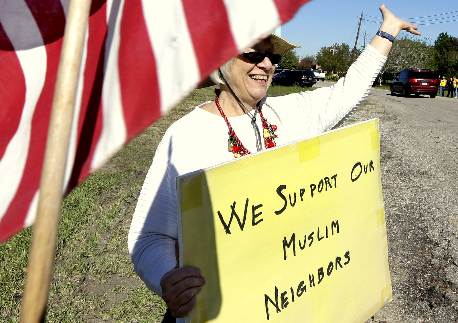 Jane Malin holds a sign as she waves to passing cars during a rally to show support for Muslim members of the community. (AP Photo/David J. Phillip)