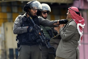 A Palestinian is pushed an Israeli policemen. Saturday, Oct. 10, 2015. (AP Photo/Nasser Shiyoukhi)