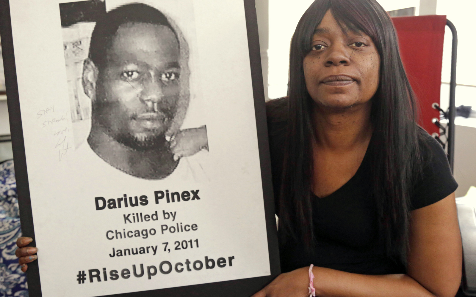 Gloria Pinex holds a photo of her son, Darius Pinex, at her home in Chicago. Pinex sued the city after her son was killed by police in 2011 and on Monday, Jan. 4, 2016, a judge accused a city prosecutor of lying, prompting the city's law department to examine dozens of other cases the attorney worked on. (AP Photo/M. Spencer Green)