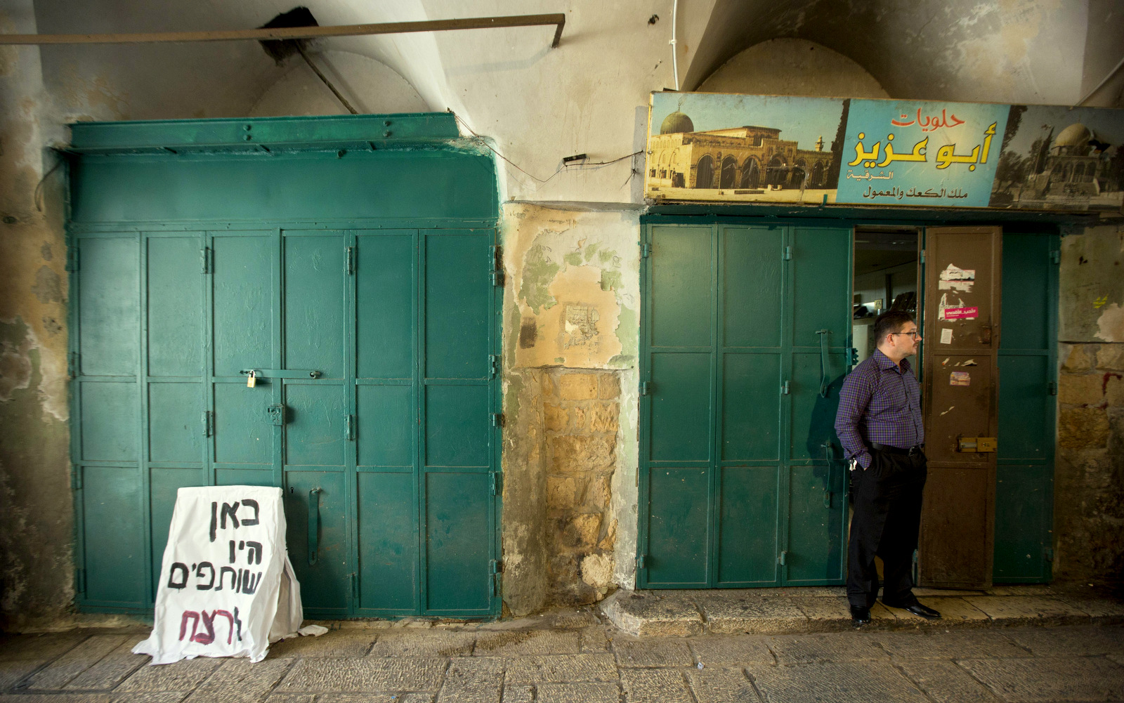 A Palestinian vendor stands outside his shop Jerusalem's Old City, Thursday, Oct. 8, 2015.  (AP Photo/Sebastian Scheiner)