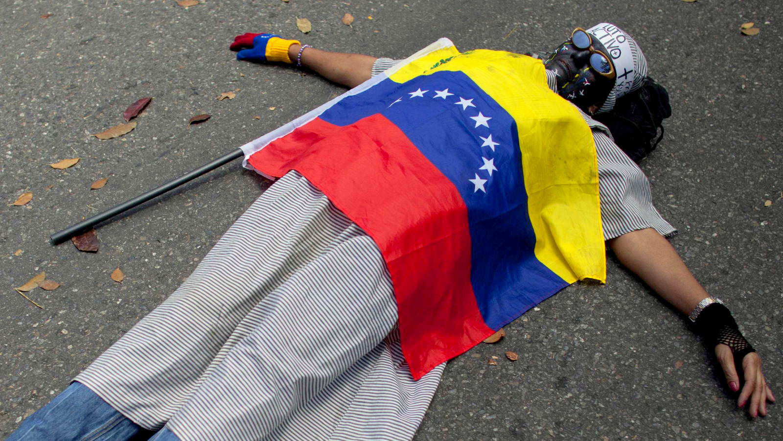 A protester covered by the Venezuelan flag lies on the ground during a protest against violence outside the Vatican's diplomatic mission in Caracas, Venezuela, Wednesday, Feb. 25, 2015. (AP Photo/Ariana Cubillos)