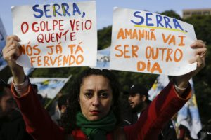 "A woman holds up signs that say in Portuguese ""Serra, the coup is hot, we're already boiling,"" left, and ""Serra, tomorrow will be another day"" as protesters wait for him outside the Foreign Relations Ministry where he'll meet Argentina's Foreign Minister Susana Malcorra in Buenos Aires, Argentina, Monday, May 23, 2016. Serra is on his first state visit since being appointed in the wake of Brazilian President Dilma Rousseff's impeachment. (AP Photo/Natacha Pisarenko)"
