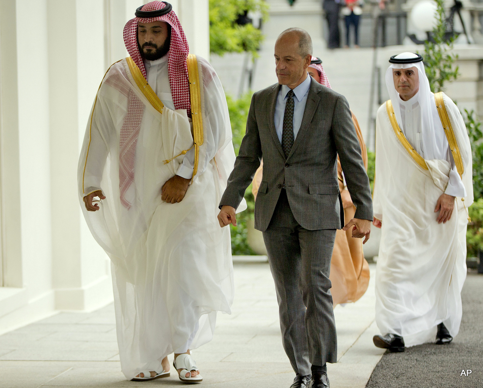 Saudi Arabia's Deputy Crown Prince Mohammed bin Salman, left, walks into the West Wing of the White House in Washington escorted by Mark E. Walsh, center, Deputy Chief of Protocol, Friday, June 17, 2016.