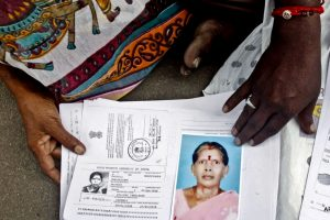 Relatives of Kasthuri Munirathinam, an Indian woman who lost an arm during an escape attempt from her Saudi employer. display a photo of her and copies of her employment documents, in Chennai, India, Oct. 24, 2015.