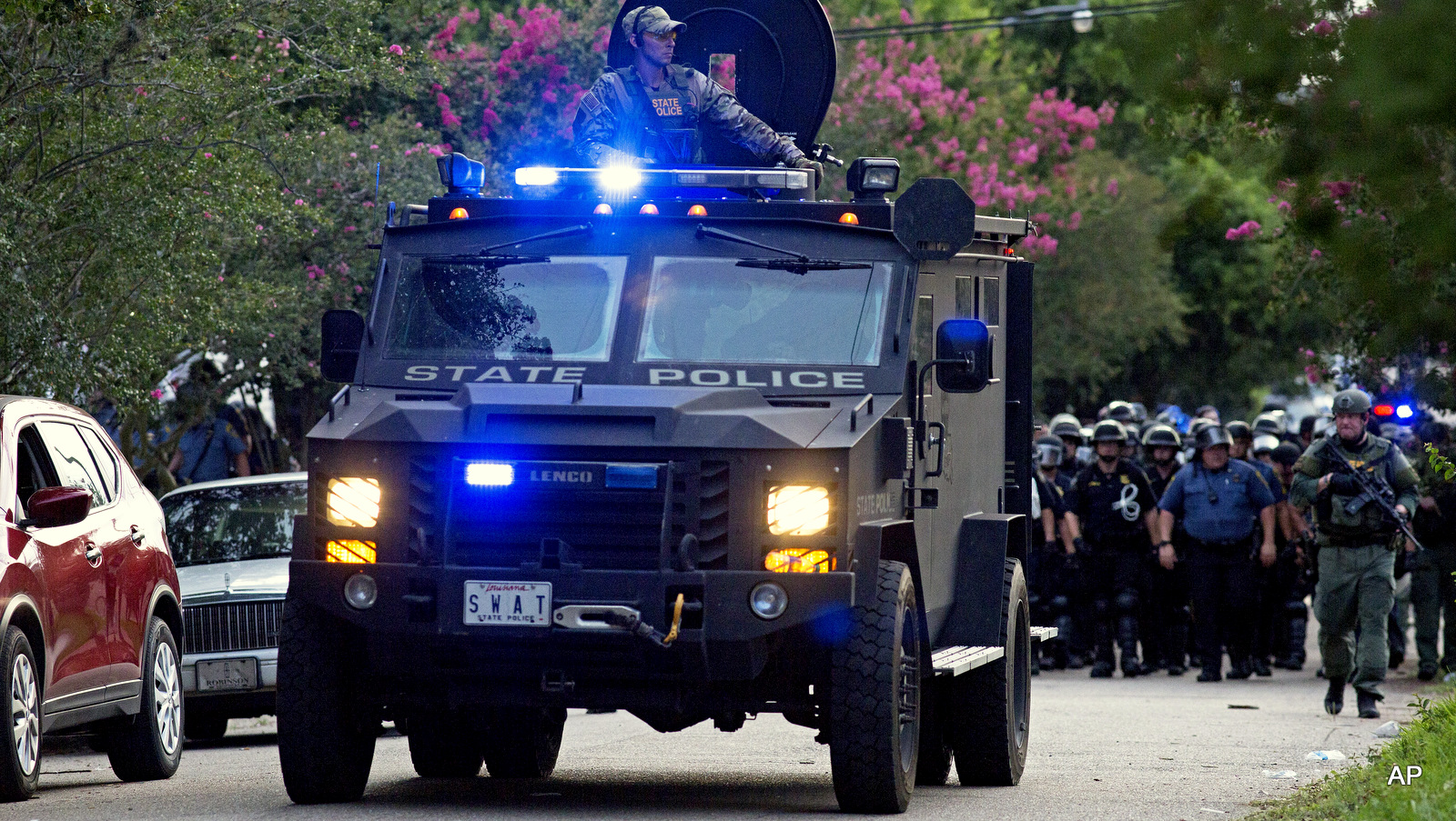 An armored police truck leads a troop of police through a residential neighborhood in Baton Rouge, La. on Sunday, July 10, 2016.