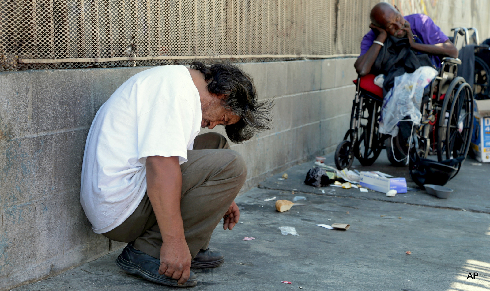 Homeless people rest in the Skid Row section of Los Angeles, Friday, Aug. 19, 2016.