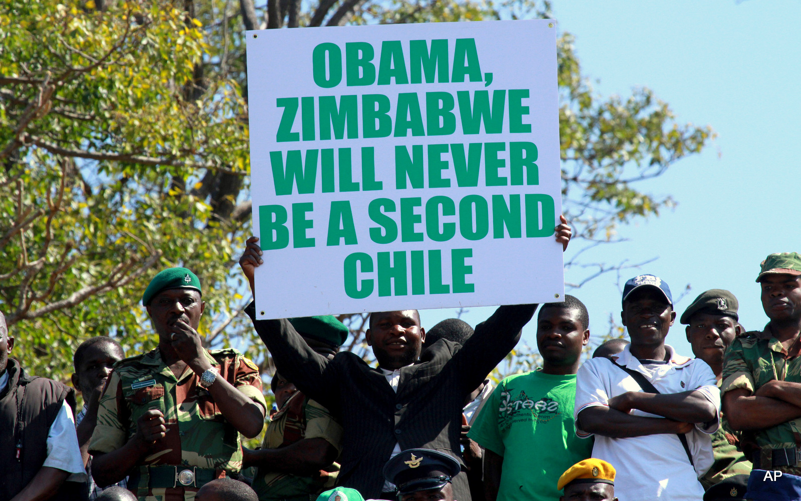 A man holds a poster with a message for United States President Barack Obama at Zimbabwe's Commemoration of Heroes day in Harare, Monday, Aug.12, 2013. Zimbabwean President elect Robert Mugabe was the guest speaker at the event. Mugabe recieved more than 60 percent of the vote in recent Presidential elections.