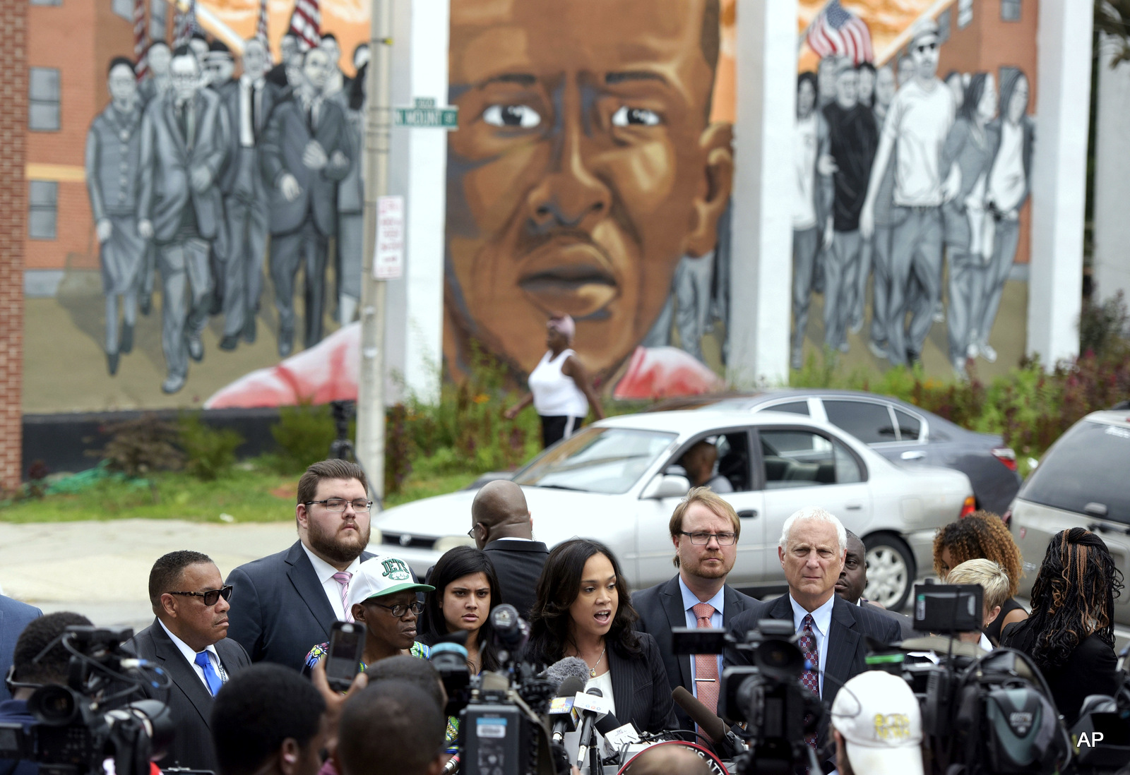 A mural depicting Freddie Gray in the background, Baltimore State's Attorney Marilyn Mosby, center, speaks during a news conference after her office dropped remaining charges against the three Baltimore police officers who were still awaiting trial in Freddie Gray' death in Baltimore.